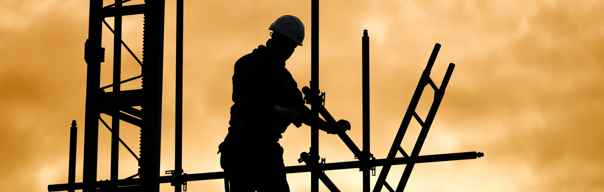 silhouette of construction worker against sky on scaffolding wit